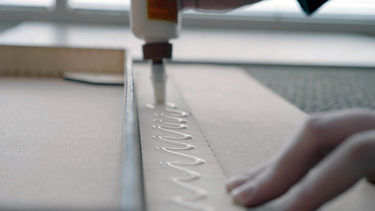 Applying glue to a laser cut piece of plywood.